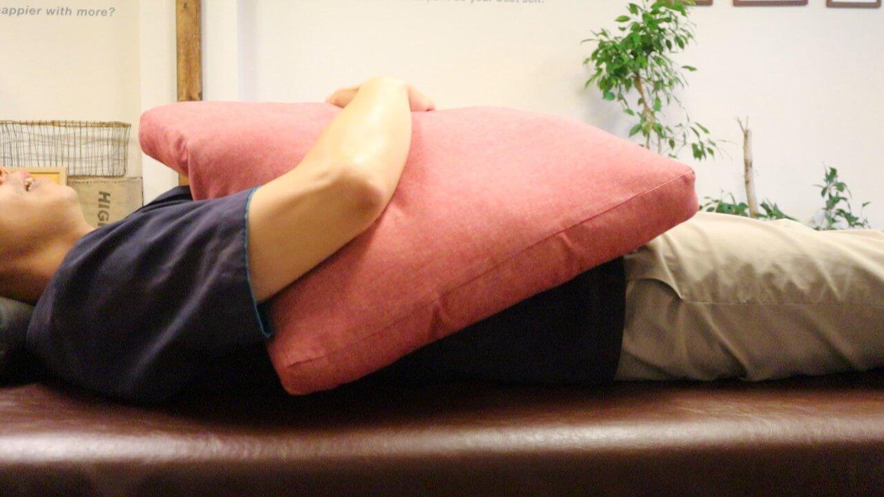クッションを抱いて寝る